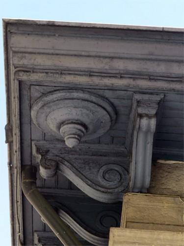 La fermeture d'avant-toit est soutenue par des modillons de bois avec ornements en forme de patère aux quatre angles