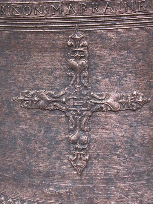 Bard (Loire), église paroissiale Saint-Jean. Détail de la cloche de 1647 : croix avec monogramme IHS